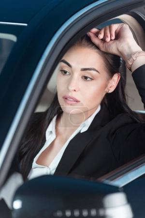 Photo pour Jeune femme pensive en costume assis dans le siège du conducteur d'une voiture particulière - image libre de droit