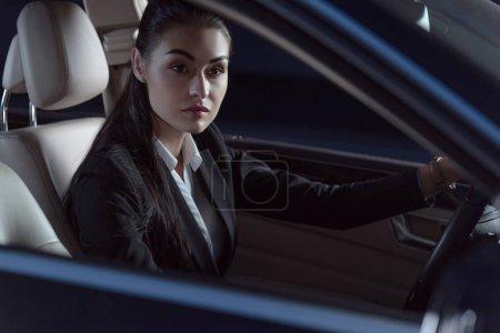 Photo pour Belle jeune femme en costume assis dans un siège du conducteur de voiture de tourisme - image libre de droit
