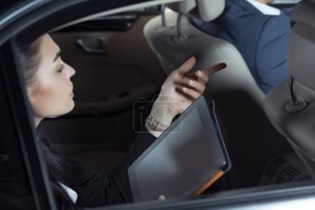 Photo pour Jeune femme en costume assis sur le siège arrière de la voiture avec tablette numérique et parler au conducteur - image libre de droit