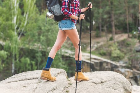 Cropped shot of woman hiking on rocky mountains...