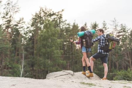 Photo pour Jeunes randonneurs avec sacs à dos, debout sur la falaise et de la recherche. - image libre de droit