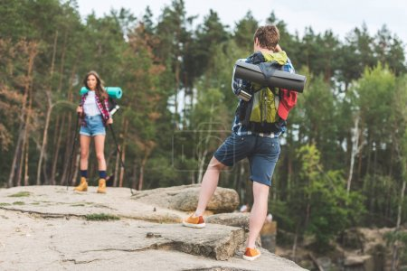 man taking photo of girlfriend in forest