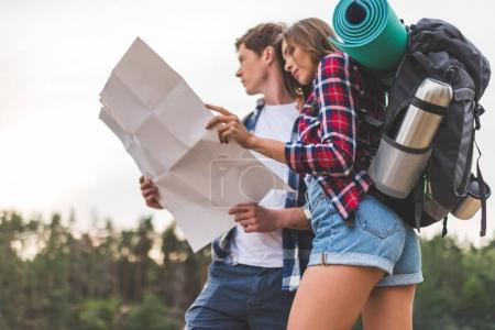Photo pour Beau jeune couple de randonneurs avec carte sur la nature - image libre de droit