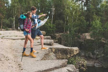 Photo for Young couple of hikers with map on nature - Royalty Free Image