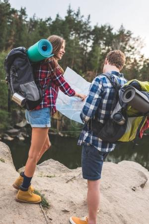 couple with backpacks looking at map