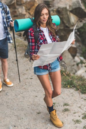 Woman hiking and navigating with map