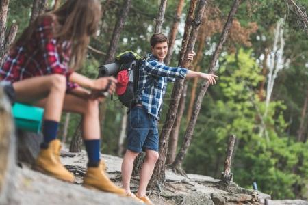 Photo pour Jeune couple avec sacs à dos en randonnée en forêt - image libre de droit