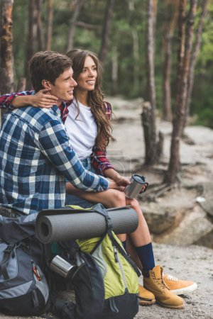 couple with backpacks relaxing in forest