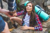 man helping girlfriend to climb rock