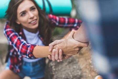 Photo pour Gros plan tourné d'homme aidant superbe copine à gravir la roche - image libre de droit
