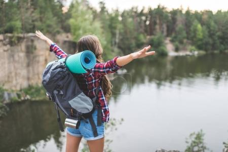 Photo for Young woman with backpack celebrating freedom on nature while looking at lake - Royalty Free Image