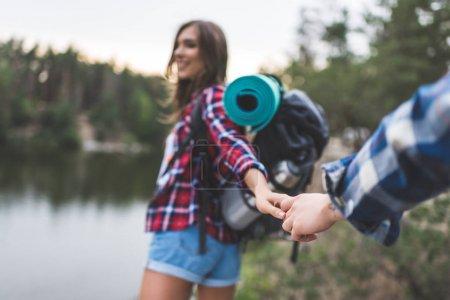 Photo pour Belle jeune femme avec son petit ami directeurs de sac à dos au lac sauvage - image libre de droit