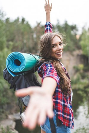Photo for Beautiful young woman with trekking backpack stretching hand out to camera outdoors - Royalty Free Image