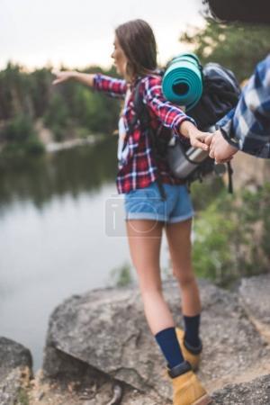 woman guiding boyfriend to wild lake