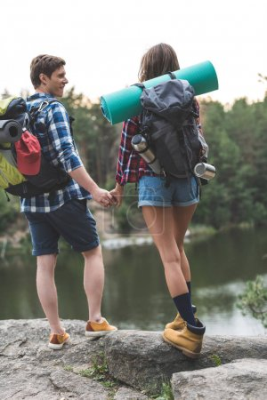 Photo for Young couple with backpacks holding hands on rocky lake shore - Royalty Free Image