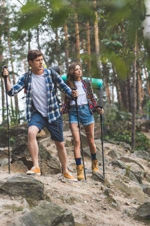 Photo pour Jeune couple actif avec bâtons de marche ayant voyage - image libre de droit