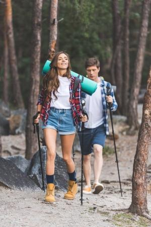 Photo for Beautiful active couple with trekking poles having trip - Royalty Free Image