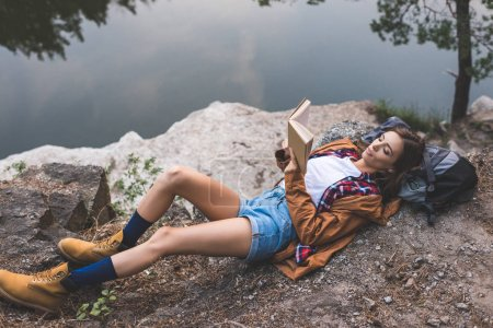 woman reading book on nature