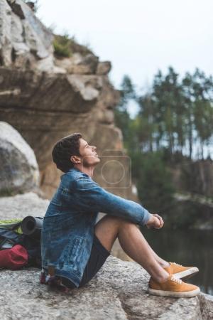 Photo pour Réfléchi jeune homme se détendre sur la falaise près du lac - image libre de droit