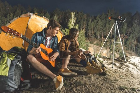 Photo for Young man playing guitar for beautiful happy girlfriend in hiking trip - Royalty Free Image