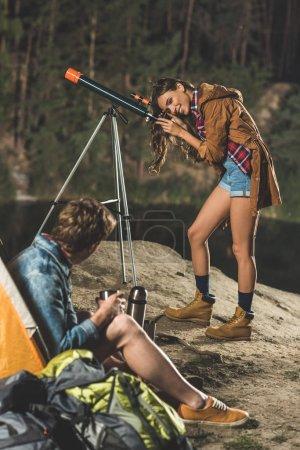 Photo pour Jeune couple heureux en voyage avec télescope près du lac de montagne - image libre de droit