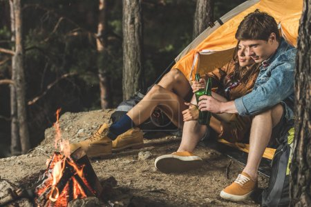couple on hiking trip drinking beer