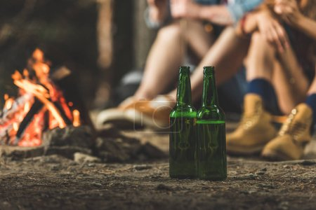 bottles of beer next to bonfire