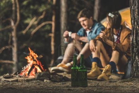 couple sitting next to hiking tent