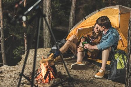 Photo for Young couple on hiking trip drinking beer in tent - Royalty Free Image