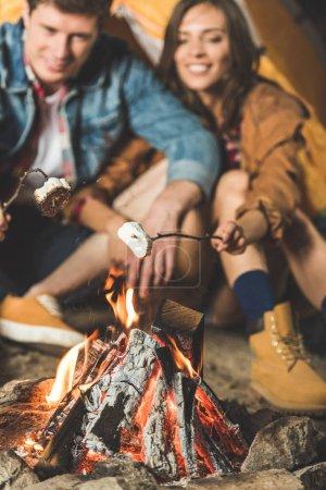 Photo pour Jeune couple torréfaction guimauve sur bâtons en voyage de camping - image libre de droit