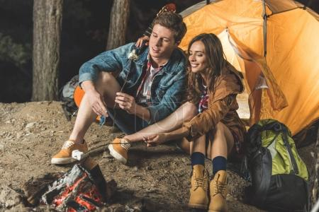 Photo for Couple roasting marshmallow on sticks in camping trip - Royalty Free Image