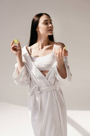 Woman holding slices of cucumber