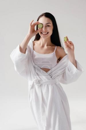 Smiling woman holding slices of cucumber
