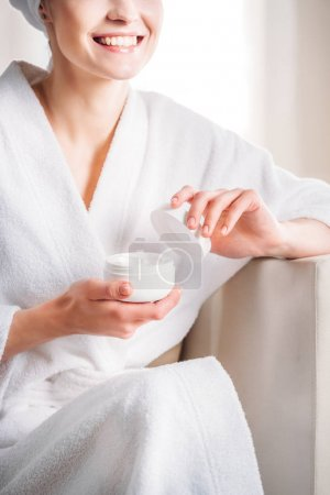 woman opening jar of cream