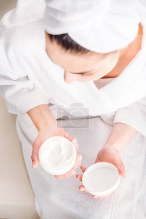 Woman opening jar of cream