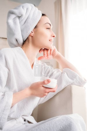 Woman holding jar of cream
