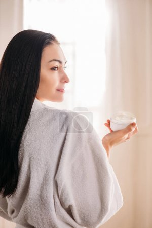 Woman in bathrobe holding jar of cream
