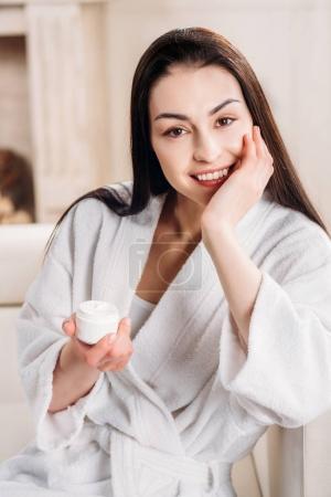woman holding jar of cream