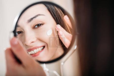 Photo for Smiling woman looking into hand mirror and applying face cream - Royalty Free Image