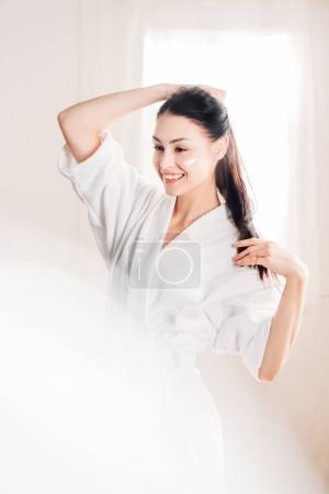 Smiling woman in bathrobe with cream on face