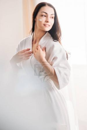 Relaxed woman in bathrobe with cream on face
