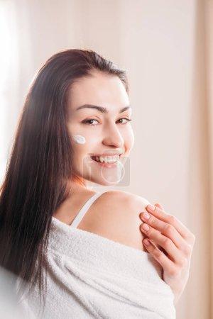 Photo pour Portrait de jeune femme heureuse avec crème appliquée à son visage regardant la caméra - image libre de droit