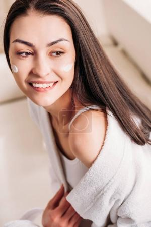 smiling woman with cream on face