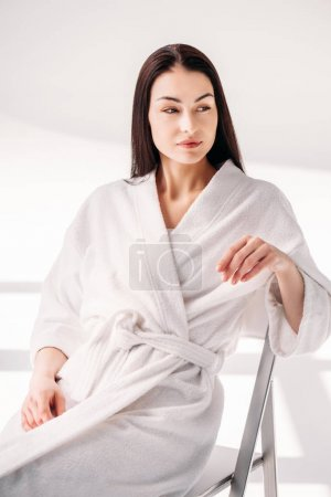 Photo for Beautiful young woman with no makeup wearing white bathrobe, sitting on chair - Royalty Free Image