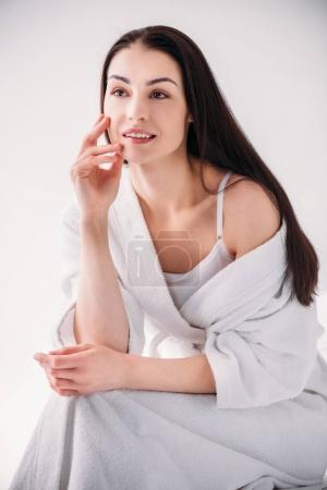 Attractive woman in bathrobe posing on chair