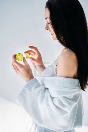 Woman in bathrobe holding slices of cucumber