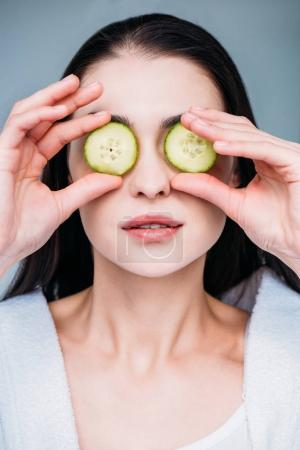 Photo for Portrait of young woman in white bathrobe holding slices of cucumber in front of eyes - Royalty Free Image
