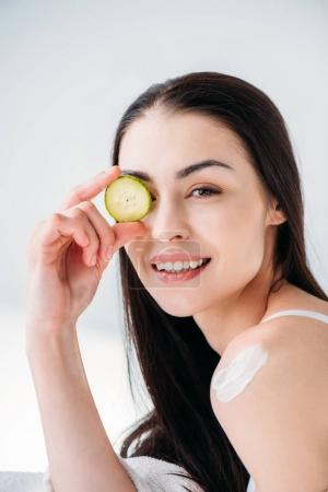 woman holding slice of cucumber on eye
