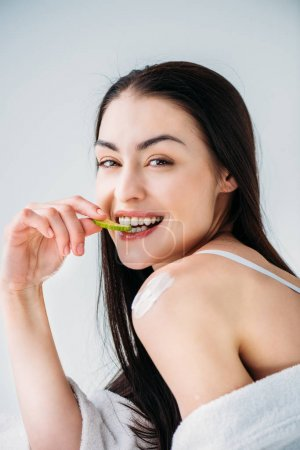 Smiling woman eating slice of cucumber