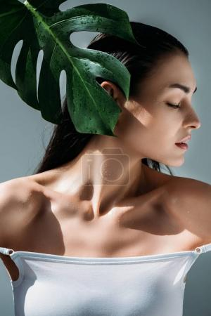Attractive woman posing with tropical leaf